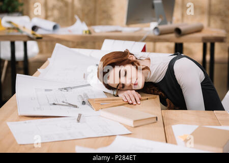 overworked female architect sleeping on building plans at workplace - Stock Photo