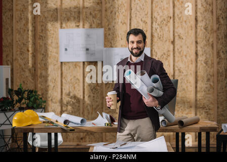 handsome young architect with coffee to go and rolled blueprints at workplace - Stock Photo