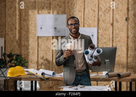 smilign african american architect with coffee to go and rolled blueprints at workplace - Stock Photo