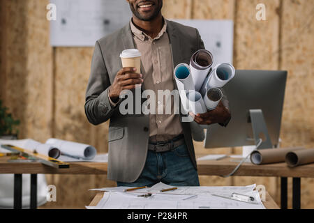 cropped shot of smiling architect with coffee to go and rolled blueprints at workplace - Stock Photo