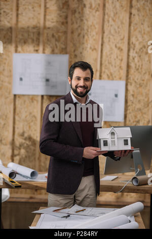 young architect with paper house model in office - Stock Photo