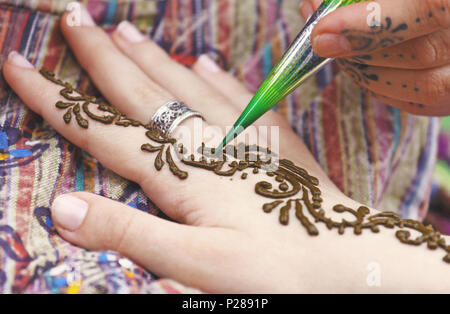 Artist painting traditional indian henna tattoo on woman hand, closeup picture, focus on mehndi artwork - Stock Photo