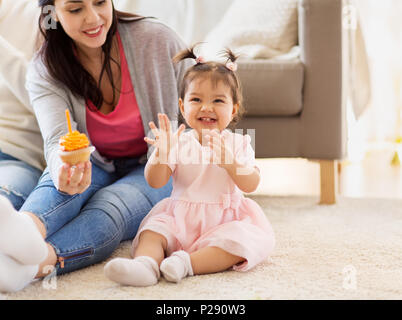 baby girl with mother at home birthday party - Stock Photo