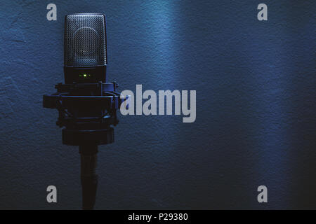 Closeup of condenser microphone on stand in front of a wall. - Stock Photo