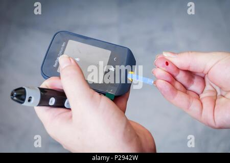 Young pregnant Caucasian woman making herself a blood sugar test with a Freestyle Optium Neo glucose meter. Pregnancy diabetes concept stock image. - Stock Photo