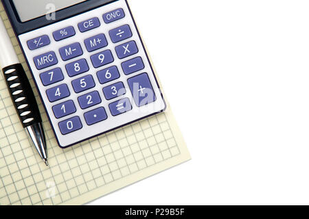 One big calculator with yellow checkbook and stationery on a white table closeup - Stock Photo