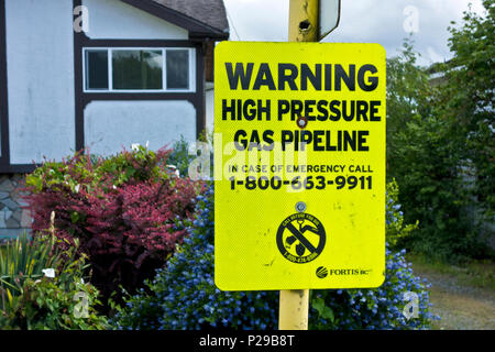 Warning sign for an underground high pressure natural gas pipeline (Fortis BC) in a North Burnaby neighbourhood.  Metro Vancouver Canada. - Stock Photo