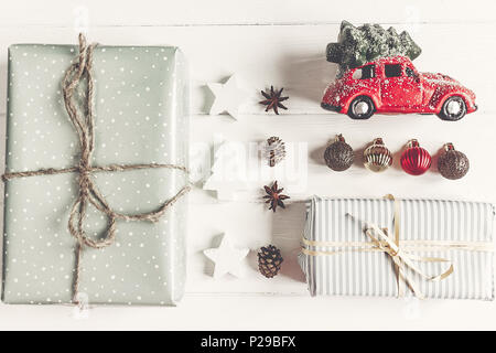merry christmas concept, flat lay. modern presents with car carrying tree, ornaments  on rustic white wood top view. seasonal greetings. happy holiday - Stock Photo