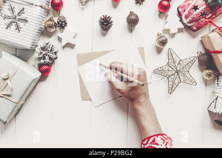 child writes letter to Santa Claus top view. kid hands holding pencil and making wish list and paper with christmas decorations and ornaments and pres - Stock Photo
