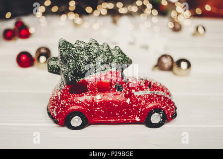 christmas present. red car toy with christmas tree on top on white wood with lights in background, space for text. seasonal greetings. happy holidays. - Stock Photo
