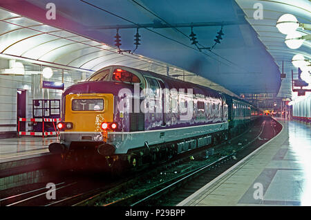 """A class 55 Deltic diesel locomotive number D9016 (55016) """"Gordon Highlander"""" waits for the booked departure time with a Steam Dreams charter. At this time the locomotive was owned by Porterbrook and carried the companies distinctive purple livery. London Liverpool Street. 5th December 2002. - Stock Photo"""