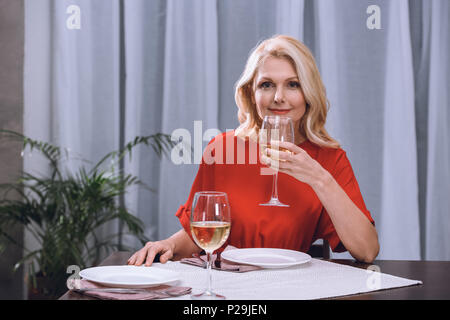 attractive woman in red dress drinking wine at table - Stock Photo