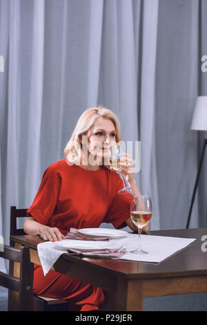 beautiful woman in red dress drinking wine at table - Stock Photo
