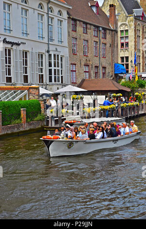 One of the very popular canal boats takes a group of tourists & visitors on a canal tour of the centre of Bruges or Brugge, Belgium - Stock Photo