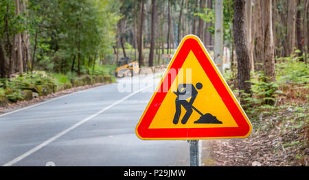 worn temporary road sign showing work on a small road in the forest - Stock Photo