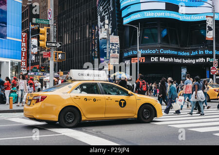 Yellow taxi waiting on the traffic light in New York, pedestrians crossing in front of it. - Stock Photo