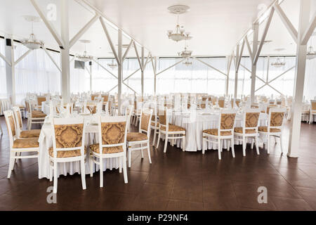 catering, party, engagement concept. there is spacious hall of the restaurant decorated in white coloures for happy day of loving couple, all tables a - Stock Photo