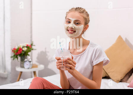 smiling young woman with white clay facial mask with milkshake in mason jar at home - Stock Photo