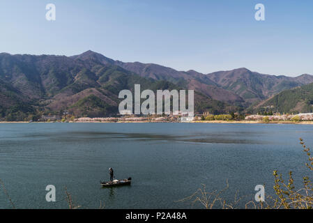 Lone fisherman on a boat on Lake Kawaguchi, Yamanashi Prefecture, Japan - Stock Photo