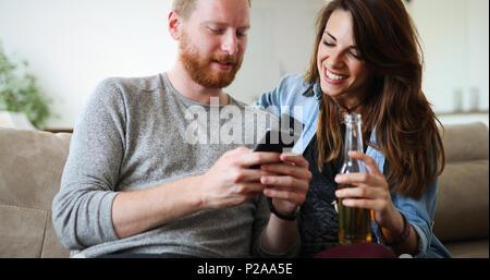 Cheerful couple laughing watching smart phone - Stock Photo