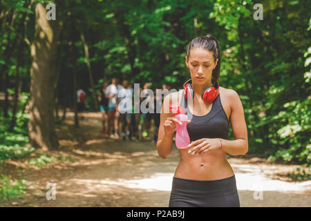 Young athlete walking in woods and holding bottle of water. Group of runners in the background. - Stock Photo