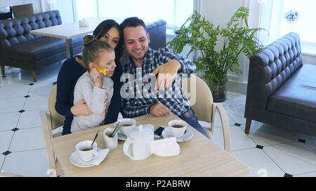 Happy father takes selfie photo with his wife and daughter during their tea time in cafe or restaurant. - Stock Photo