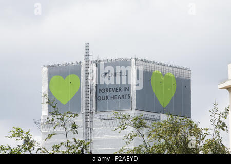 London UK. 14th June 2018.  The Grenfell  Tower covered in white tarpaulin with the message 'Forever in Our Hearts on the  One Year anniversary after the devastating fire  in West London which claimed the lives of 72 residents in the tower block.  A minute's silence will be observed nationally at midday to remember the victims of the Grenfell fire on 14 June 2017. Credit: amer ghazzal/Alamy Live News - Stock Photo
