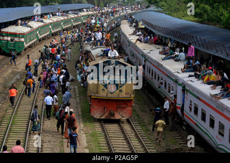 Dhaka, Bangladesh . 14th June, 2018. People sit on the roof of train carriages as they head to their homes to celebrate Eid al-Fitr from Dhaka, Bangladesh , Bangladesh, on June 14, 2018. As the Eid al-Fitr festival knocking at the door, the long distance bus stations, ferry terminals and train stations in Bangladesh capital Dhaka, Bangladesh  see overflowing with tens of thousands of home-bound passengers. Credit: Xinhua/Alamy Live News - Stock Photo