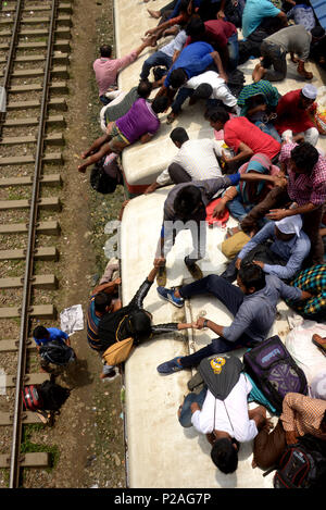 Dhaka, Bangladesh . 14th June, 2018. People try to climb on the roof of train carriages as they head to their homes to celebrate Eid al-Fitr from Dhaka, Bangladesh , Bangladesh, on June 14, 2018. As the Eid al-Fitr festival knocking at the door, the long distance bus stations, ferry terminals and train stations in Bangladesh capital Dhaka, Bangladesh  see overflowing with tens of thousands of home-bound passengers. Credit: Xinhua/Alamy Live News - Stock Photo
