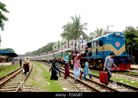 Dhaka, Bangladesh . 14th June, 2018. People cling to carriages of a train as they head to their homes to celebrate Eid al-Fitr from Dhaka, Bangladesh , Bangladesh, on June 14, 2018. As the Eid al-Fitr festival knocking at the door, the long distance bus stations, ferry terminals and train stations in Bangladesh capital Dhaka, Bangladesh  see overflowing with tens of thousands of home-bound passengers. Credit: Xinhua/Alamy Live News - Stock Photo