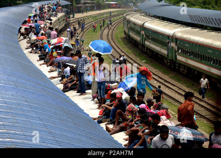 Dhaka. 14th June, 2018. People sit on the roof of train carriages as they head to their homes to celebrate Eid al-Fitr from Dhaka, Bangladesh, on June 14, 2018. As the Eid al-Fitr festival knocking at the door, the long distance bus stations, ferry terminals and train stations in Bangladesh capital Dhaka see overflowing with tens of thousands of home-bound passengers. Credit: Xinhua/Alamy Live News - Stock Photo