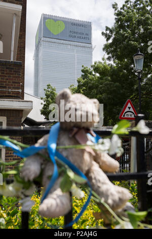 London, UK. 14th Jun, 2018.  Childrens' bears and cuddly toys on railings near where the Grenfell fire occured, on the first anniversary of the tower block disaster. 72 people died when the tower block in the borough of Kensington & Chelsea were killed in what has been called the largest fire since WW2. The 24-storey Grenfell Tower block of public housing flats in North Kensington, West London, United Kingdom. It caused 72 deaths, out of the 293 people in the building, including 2 who escaped and died in hospital. Over 70 were injured and left traumatised. Credit: RichardBaker/Alamy Live News - Stock Photo