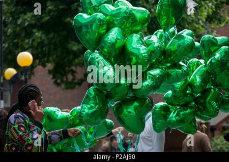 London, UK. 14th Jun, 2018.  Green heart-shaped balloons during the memorial service for the Grenfell fire on the first anniversary of the tower block disaster. 72 people died when the tower block in the borough of Kensington & Chelsea were killed in what has been called the largest fire since WW2. The 24-storey Grenfell Tower block of public housing flats in North Kensington, West London, United Kingdom. It caused 72 deaths, out of the 293 people in the building, including 2 who escaped and died in hospital. Over 70 were injured and left traumatised. Credit: RichardBaker/Alamy Live News - Stock Photo