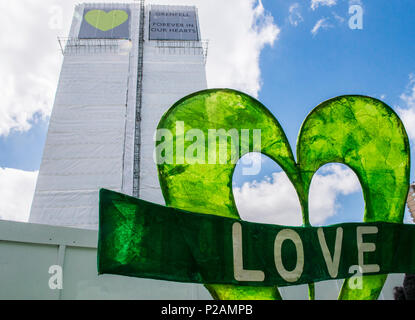 A giant banner with the word Love is left at the base of the Grenfell Tower to mark the anniversary of the fire, London, England, UK, 14th June 2018 - Stock Photo
