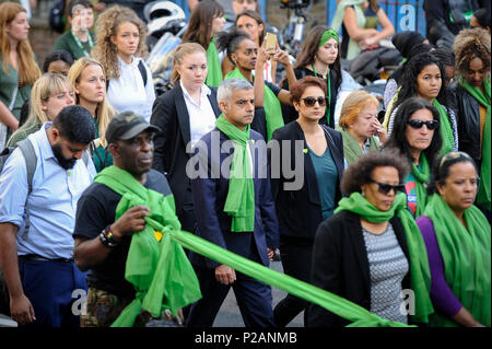 London, UK.  14 June 2018.  Sadiq Khan, Mayor of London (C) and his wife take part in a silent march to commemorate the victims of the fire. Tributes are taking place in the local area to remember the 72 people who were killed on the one year anniversary of the Grenfell Tower tragedy where a small kitchen fire turned into the biggest blaze seen in the UK since the Second World War. Many people are wearing green scarves - Green For Grenfell - in memory of those lost.  Credit: Stephen Chung / Alamy Live News - Stock Photo