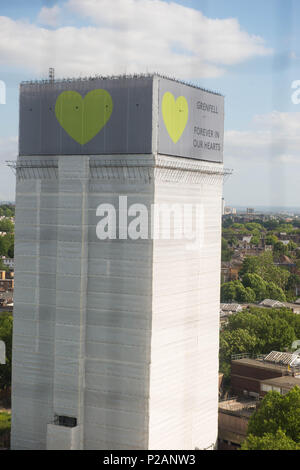 London, England. 14th June 2018.A sign with 'Grenfell Forever In Our Hearts' is displayed on the top of Grenfell Tower. Silent walk is held to mark the first anniversary of the Grenfell Tower fire, which claimed the lives of 72 people. ©Michael Tubi/Alamy Live News - Stock Photo
