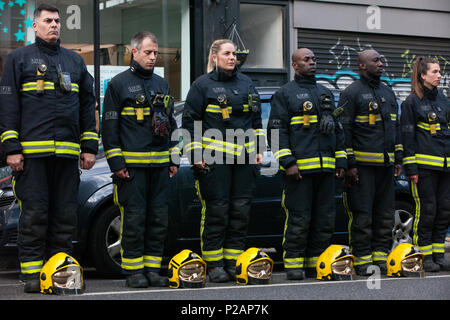 London, UK. 14th June, 2018. A guard of honour prepared by the London Fire Brigade for the Grenfell Silent March through West Kensington on the first anniversary of the Grenfell Tower fire. 72 people died in the Grenfell Tower fire and over 70 were injured. Credit: Mark Kerrison/Alamy Live News - Stock Photo