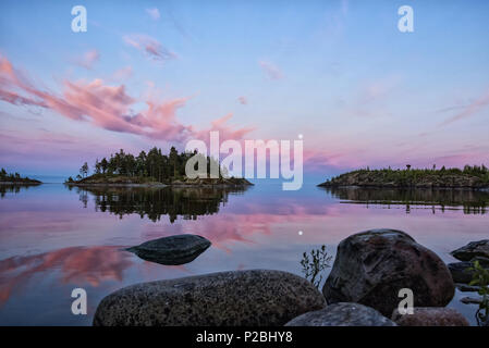 Spectacular blue hour landscape, just after sunset. Pink clouds and full moon are reflected in Ladoga lake, located in Karelia, north of Russia. Selec - Stock Photo