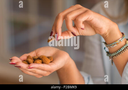 Young woman hands holding nuts at the kitchen. Close up. Healthy concept. - Stock Photo