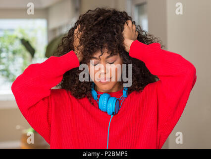 African american woman wearing headphones suffering from headache desperate and stressed because pain and migraine. Hands on head. - Stock Photo
