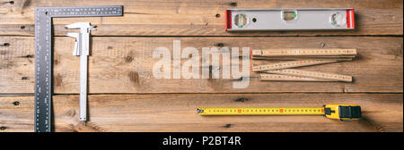 Carpentry tools. Measure tape, spirit level and rulers on wooden background, banner, copy space, top view - Stock Photo