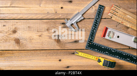Carpentry tools. Measure tape, spirit level and rulers on wooden background, copy space, top view - Stock Photo