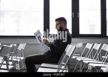side view of focused businessman reading newspaper while sitting in meeting room - Stock Photo
