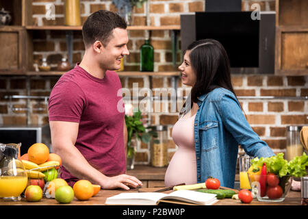 side view of happy young pregnant couple smiling each other while cooking together at kitchen - Stock Photo