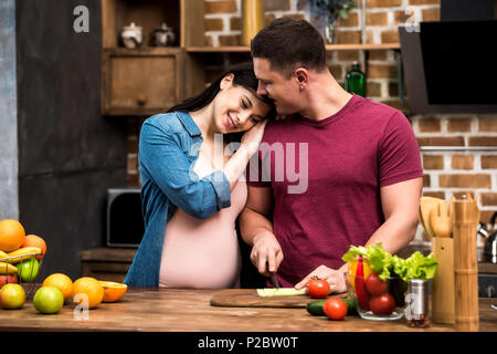 happy young pregnant couple standing together while cooking at kitchen - Stock Photo