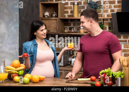 happy young pregnant couple smiling each other while cooking together at kitchen - Stock Photo