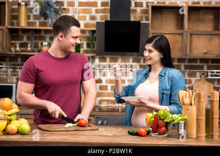 happy young pregnant couple smiling each other while cooking together - Stock Photo