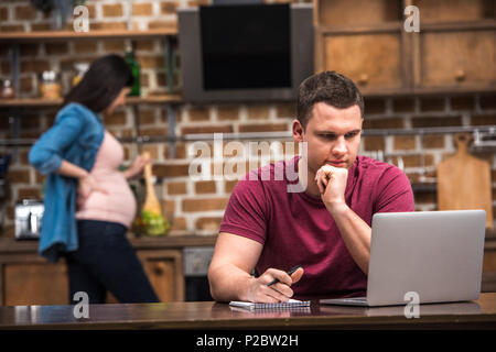 focused young man using laptop and taking notes while pregnant wife cooking behind - Stock Photo
