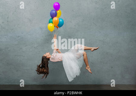 young woman levitating with colorful balloons - Stock Photo