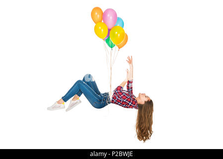 young woman levitating with colorful balloons isolated on white - Stock Photo